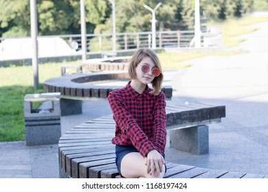 Portrait of beautiful teenage girl sitting on bench in city park. Pretty model with short hairstyle and fashionable outfit. Weekend concept. Blurred background