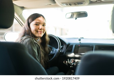 Portrait of a beautiful teenage girl smiling before starting her car and going out. Adolescent girl feeling happy to drive after getting her license