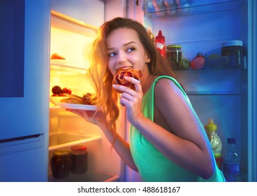 Portrait Of Beautiful Teenage girl Taking Food From Refrigerator at night. Night eating, overeat concept. Diet, dieting. Beauty young woman eating pastries in fridge at night kitchen