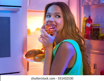 Portrait Of Beautiful Teenage girl Taking Food From Refrigerator at night. Night eating, overeat concept. Diet, dieting. Beauty young woman eating pastries in fridge at night kitchen.
