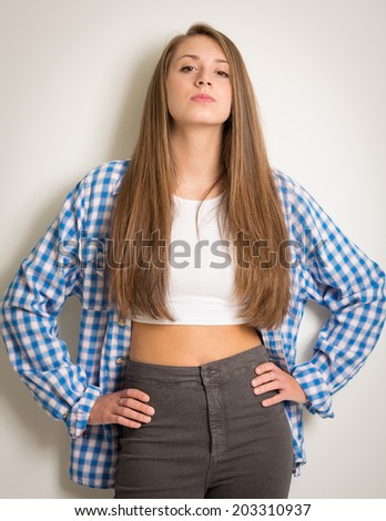 9579181e5712c Portrait of a beautiful teenage girl in a white top and blue shirt with long  brown hair isolated against a light grey background wearing grey trousers -  ...