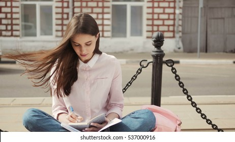 Portrait of a beautiful teenage student girl sitting with copy book and studing. Sunny summer day. Modern  casual lifestyle. Woman  note pad.
