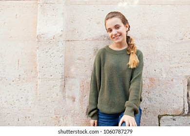 Portrait of beautiful teenager girl leaning on textured stone wall outdoors, looking smiling at camera. Young friendly woman face, tourist student recreation lifestyle, simple beauty portrait.