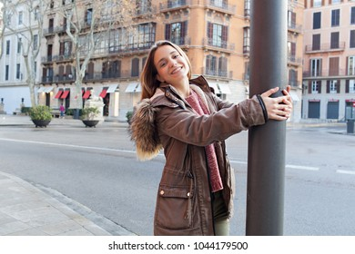 Portrait of beautiful teenager girl visiting city on holiday, joyful playful looking smiling at camera, outdoors. Tourist young woman with classic architecture buildings, leisure recreation lifestyle.