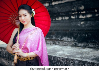 Portrait of beautiful Thai woman in Thai national dress standing at the temple with red umbrella. She is smiling and looking forward.