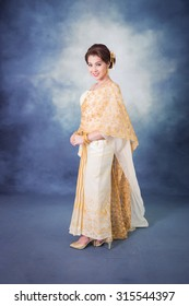 portrait beautiful thai woman in vintage thai traditional costume,white and gold color dress,smiling in studio light
