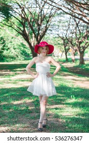 Portrait of Beautiful thai woman in white dress gold hairs wear red hat stand  under tunnel tree in the sunny day,bright sunlight