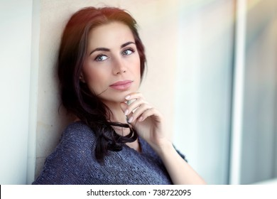 Portrait of a beautiful thoughtful woman outdoors, gorgeous model with natural makeup in bright sunlight, authentic beauty of a young female