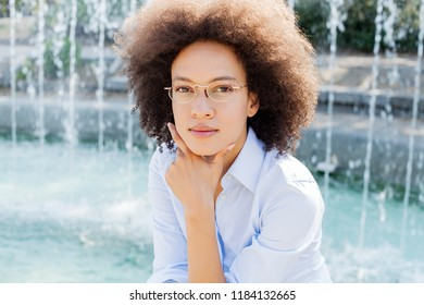 Portrait Of Beautiful Thoughtful Young Afro American Woman With Glasses Outdoor, Casual Wear, Looking At The Camera