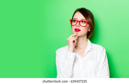 portrait of beautiful thoughtful young woman in glasses on the wonderful studio green background
