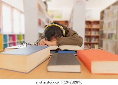 portrait of beautiful tired brunette student girl sitting among the books