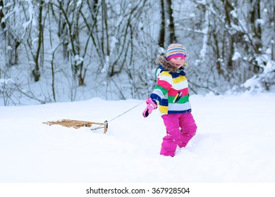Portrait of beautiful toddler girl playing outdoors with snow. Happy little child wearing colorful knitted hat and blue coat enjoying winter day in the park or forest.