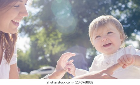 Portrait of beautiful toddler laughing and smiling with their mother outdoors
