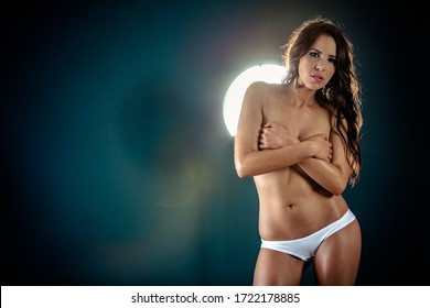 Portrait of a beautiful topless young woman covering her breasts with hands