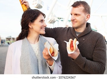 Portrait of beautiful tourist couple in fun fair activities, smiling together eating hot dog fast food outdoors. Man and woman holding junk food in amusement park, recreation leisure lifestyle.