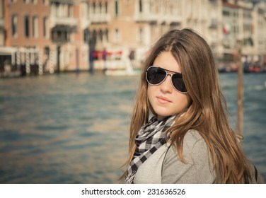 Portrait of a beautiful tourist girl with long hair in sunglasses with the Grand Canal in the background. Venice. Italy