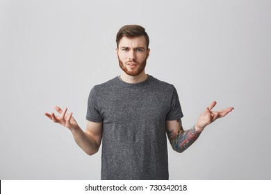 Portrait of beautiful unhappy caucasian man with beard, stylish hairstyle, and bright tattoo on left arm spreading hands with unsatisfied expression seeing friend with his girlfriend.