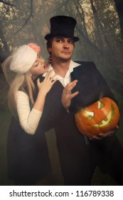 Portrait of a beautiful  vampire couple in medieval costumes with Halloween pumpkin in forest