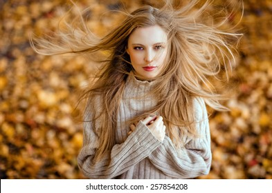 Portrait of a beautiful very cute girl with long straight hair, which flutter in the wind ; knitted sweater in autumn