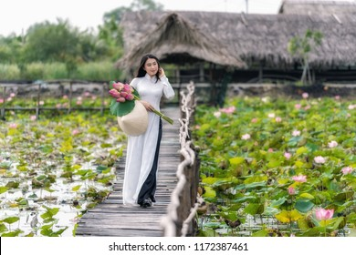 Portrait of beautiful vietnamese woman with traditional vietnam hat holding the pink lotus walking on the wooden bridge in big lotus lake, vietnam, aisan or southeast asia travel concept