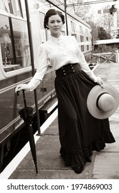 Portrait of beautiful vintage woman standing on platform with hat and umbrella