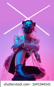 Portrait of beautiful virus mask Asian woman wearing face protection and raincoat around colourful bright neon uv lights posing in studio