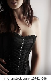 Portrait of a beautiful, voluptuous and sexy caucasian adult woman in black lace up corset in a boudoir setting lit from the side with window light.