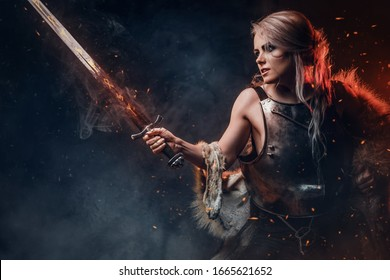 Portrait of a beautiful warrior woman holding a sword wearing steel cuirass and fur. Fantasy fashion. Studio photography on a dark background.