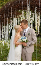 Portrait of beautiful wedding couple. Happy bride and groom near the wedding arch in rustic style for the wedding ceremony