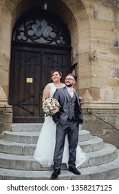 Portrait of a beautiful wedding couple. They are standing on a stairs near an old building, a bride embracing her groom. They are looking away and smiling.