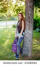 Portrait of beautiful white Caucasian young woman with long red hair, standing with backpack  in park outside at sunset. Autumn fall back-to-school concept. Schoolgirl student.