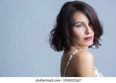 Portrait of a beautiful white girl with black hair dressed in a white striped jumpsuit, isolated on gray background