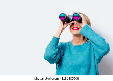 Portrait of a beautiful white smiling woman in blue sweater with binocular on white background, isolated.