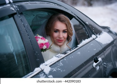 Portrait of a beautiful wife looks out the car window wedding