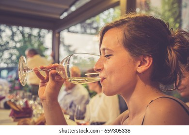 portrait of a beautiful wine tasting tourist woman in a restaurant
