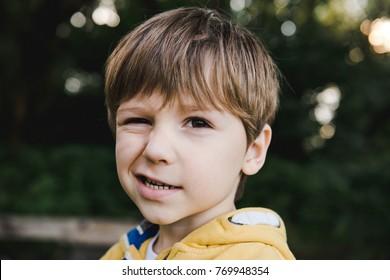 Portrait of beautiful winking little boy in a yellow sweater. A boy winking.