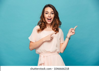 Portrait of beautiful woman 20s wearing adorable dress expressing happiness while pointing fingers aside on copyspace isolated over blue background