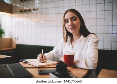 Portrait of beautiful woman 20s writing plan for tomorrow in textbook while posing and looking at camera indoors, clever hipster girl learning at university campus having break for drinking coffee