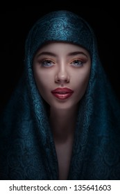 Portrait of a beautiful woman with arabian makeup in paranja isolated on dark background