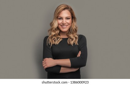 Portrait of a beautiful woman. Attractive blonde in dark clothes on a gray background. Toned photo.