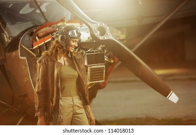 Portrait of beautiful woman aviator in airport at sunset