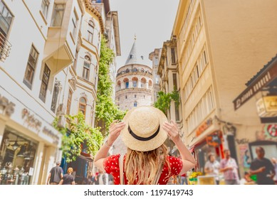 Portrait of beautiful woman backside with view of Galata tower in Beyoglu,Istanbul,Turkey