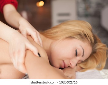 Portrait of beautiful woman , beauty, spa, healthy lifestyle and relaxation concept - close up of beautiful young woman lying with closed eyes and having hand massage in spa salon