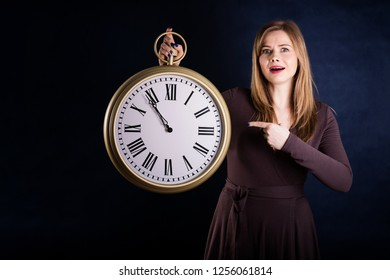 Portrait of beautiful woman with big clock on a dark blue background. Isolated.