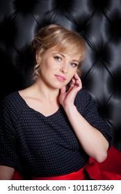 Portrait of a beautiful woman in a black dress, studio shot