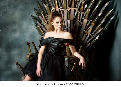 Portrait of beautiful woman in black dress sitting on a swords throne at studio background.