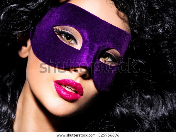 Portrait of a beautiful  woman with black hairs and violet mask on face. Purple nails.