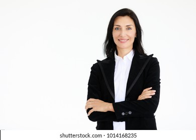 Portrait of beautiful woman in black suit standing in front of white background with self confident manner