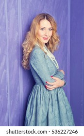 Portrait of a beautiful woman with blonde curling hair in a blue dress. Fashion photo
