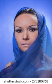 Portrait of the beautiful woman with a blue veil